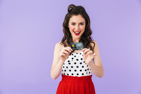 Portrait of joyful pin-up woman 20s in vintage polka dot dress smiling while holding plastic credit card isolated over violet background