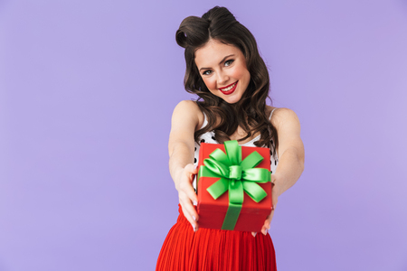 Portrait of brunette pin-up woman 20s in retro polka dot dress rejoicing while holding birthday present box isolated over violet background
