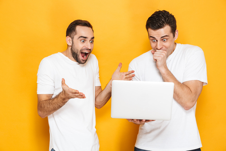 Two cheerful excited men friends wearing blank t-shirts standing isolated over yellow background, using laptop computer, celebrating success