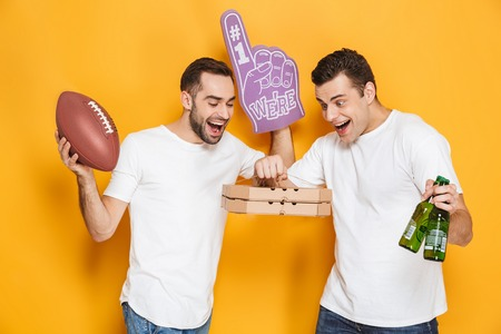 Two cheerful excited men friends wearing blank t-shirts standing isolated over yellow background, watching footbal with pizza and beer Stock Photo