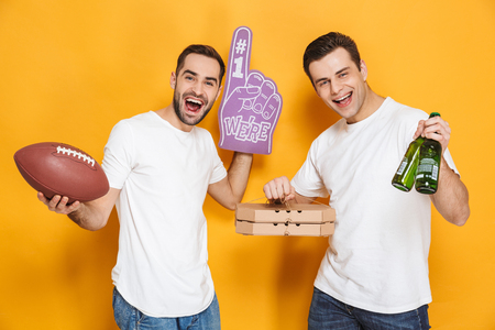 Image of two optimistic men 30s in white t-shirts holding rugby ball and number one fan hand glove while standing isolated over yellow background