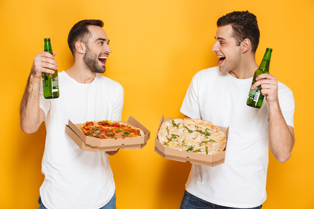 Two cheerful excited men friends wearing blank t-shirts standing isolated over yellow background, watching footbal with pizza and beer 免版税图像