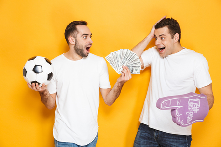 Two cheerful excited men friends wearing blank t-shirts standing isolated over yellow background, cheering with foam glove and football, showing money banknotes 免版税图像