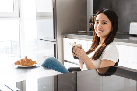 Portrait of adorable asian girl 20s drinking tea and holding mobile phone in hand while having breakfast in kitchen at home