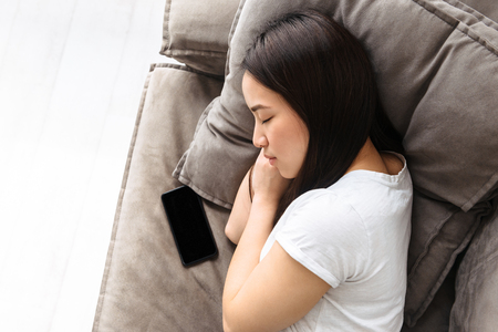 Image of charming asian girl 20s with dark long hair lying and sleeping on sofa with smartphone in bright room at home 写真素材