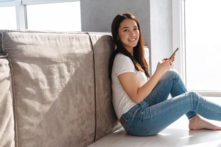 Portrait of pleased asian girl 20s wearing casual jeans holding and using smartphone while sitting on floor at home in bright room Stock Photo