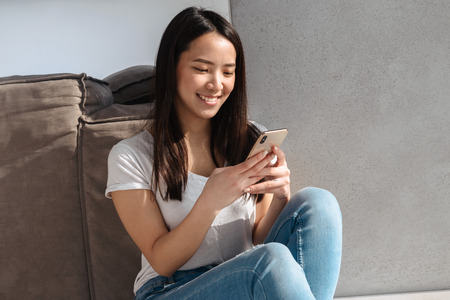 Portrait of attractive asian girl 20s wearing casual jeans holding and using smartphone while sitting on floor at home in bright room 写真素材
