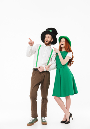 Full length of a happy young couple wearing costumes, celebrating St.Patrick 's Day isolated over white background