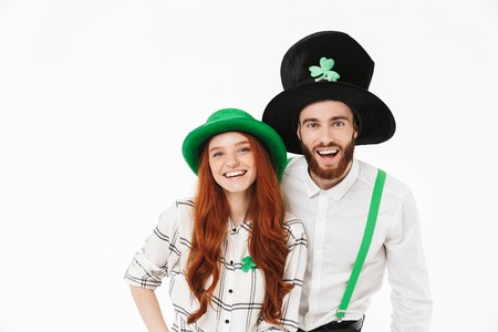 Cheerful young couple standing isolated over white background, celebrating St.Patrick s Day
