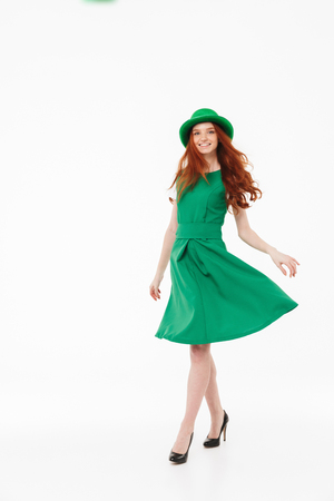 Full length of a happy young redheaded girl wearing green hat, celebrating St. Patrickss Day isolated over white background, posing Stock Photo