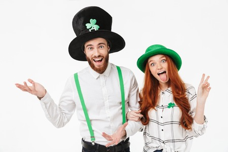 Glückliches junges Paar in Kostümen, das St.Patrick's Day isoliert auf weißem Hintergrund feiert, zusammen Spaß hat