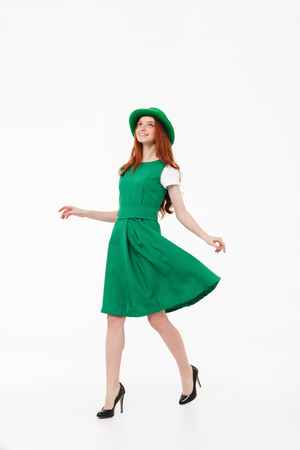 Full length of a happy young redheaded girl wearing green hat, celebrating St. Patricks's Day isolated over white background, posing