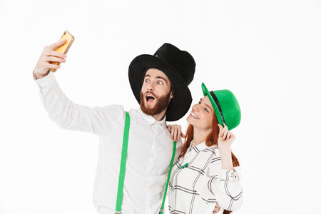 Happy young couple wearing costumes, celebrating St.Patrick s Day isolated over white background, taking a selfie