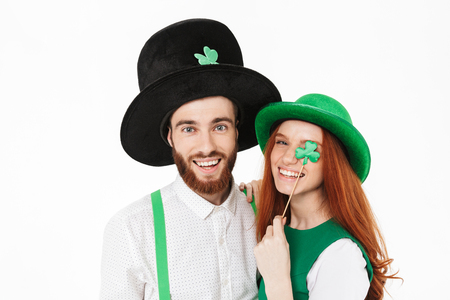 Happy young couple wearing costumes, celebrating St.Patrick 's Day isolated over white background, having fun together