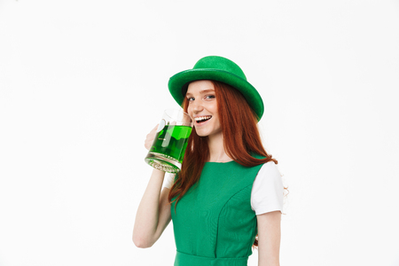 Happy young redheaded girl wearing green hat, celebrating St. Patrickss Day isolated over white background, drinking beer