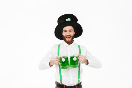 Cheerful young man celebrating St.Patrick s Day isolated over white background, drinking beer