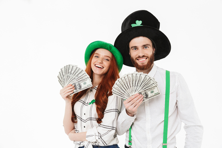 Happy young couple wearing costumes, celebrating St.Patrick s Day isolated over white background, holding money banknotes