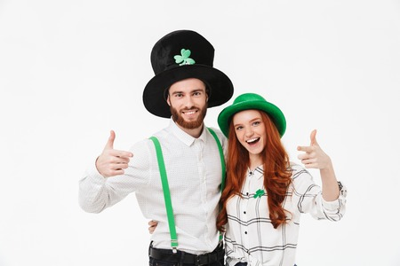 Happy young couple wearing costumes, celebrating St.Patrick s Day isolated over white background, pointing fingers