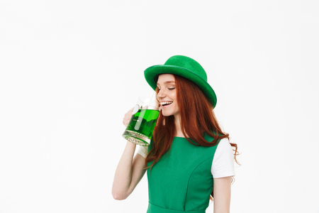 Happy young redheaded girl wearing green hat, celebrating St. Patricks's Day isolated over white background, drinking beer 写真素材