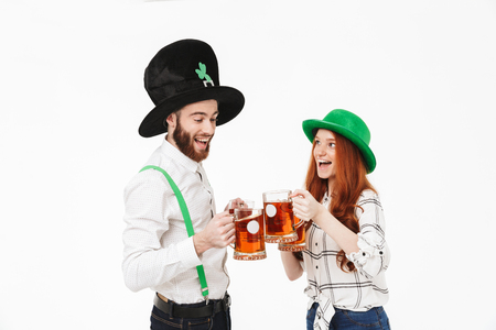 Happy young couple wearing costumes, celebrating St.Patrick s Day isolated over white background, drinking beer