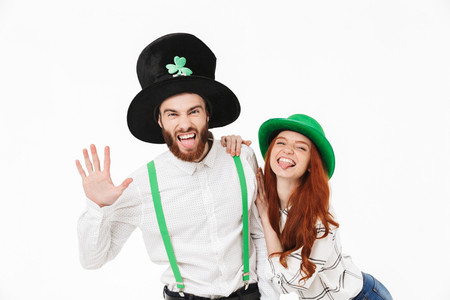 Cheerful young couple standing isolated over white background, celebrating St.Patrick 's Day Foto de archivo - 122714956