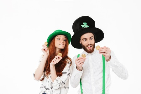 Happy young couple wearing costumes, celebrating St.Patrick s Day isolated over white background, holding golden bitcoins