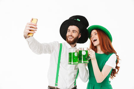 Happy young couple wearing costumes, celebrating St.Patrick 's Day isolated over white background, drinking beer