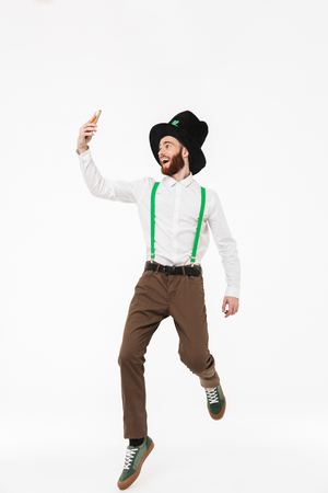 Full length of a cheerful young man celebrating St.Patrick s Day isolated over white background, taking a selfie Stockfoto
