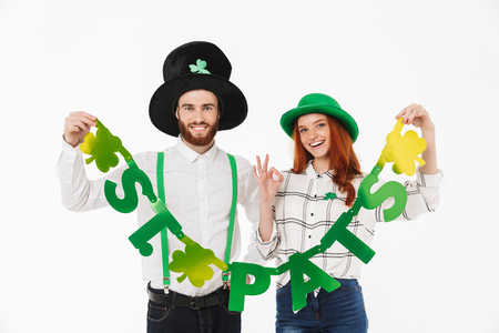 Happy young couple wearing costumes, celebrating St.Patrick s Day isolated over white background, having fun together, holding decoration