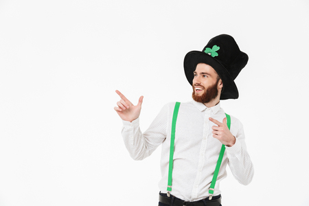 Cheerful young man celebrating St.Patrick 's Day isolated over white background, pointing finger Stockfoto - 122715104