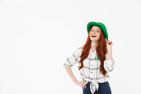 Happy young redheaded girl wearing green hat, celebrating St. Patrickss Day isolated over white background, posing