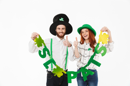 Happy young couple wearing costumes, celebrating St.Patrick 's Day isolated over white background, having fun together, holding decoration