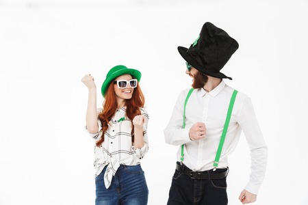 Happy young couple wearing costumes, celebrating St.Patrick s Day isolated over white background, having fun together, posing with sunglasses