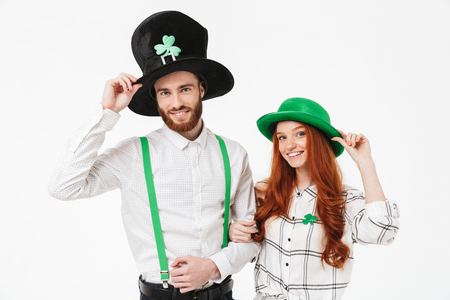 Happy young couple wearing costumes, celebrating St.Patrick 's Day isolated over white background, having fun together Imagens