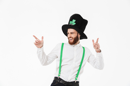 Cheerful young man celebrating St.Patrick s Day isolated over white background, pointing finger
