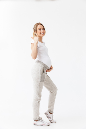 Image of a beautiful young pregnant woman posing isolated over white wall background pointing.