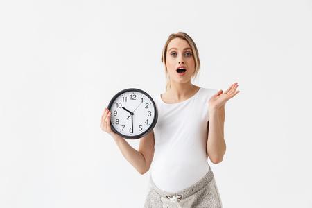 Bild einer schockierten jungen schwangeren Frau posiert isoliert über weißem Wandhintergrund mit Uhr.