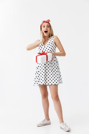 Image of excited emotional young pregnant woman posing isolated over white wall background holding present box gift.