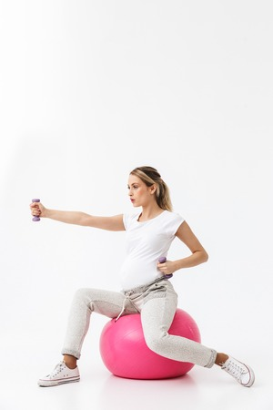 Image of a beautiful young pregnant yoga fitness woman posing isolated over white wall background make exercises with ball and dumbbell. Banco de Imagens