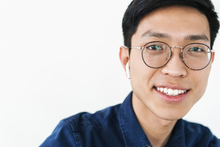 Photo closeup of content chinese man 20s wearing earpods and eyeglasses smiling while looking at camera isolated over white background