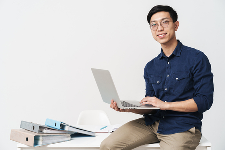 Photo of smiling asian man 20s wearing eyeglasses sitting at table and working on laptop in office isolated over white background