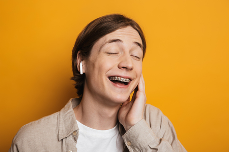 Close up image of Pleased handsome man in shirt listening music by earphones with closed eyes over yellow background