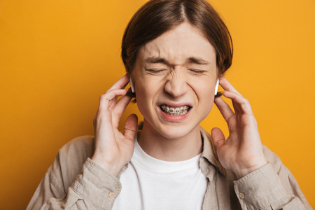 Close up image of Displeased handsome man in shirt listening music by earphones with closed eyes over yellow background