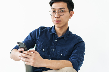 Photo of brunette chinese businessman 20s wearing eyeglasses sitting in chair and holding cell phone while working in office isolated over white background 版權商用圖片