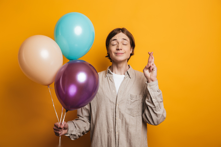 Pleased handsome man in shirt holding balloons and praying with crossed fingers gesture over yellow background