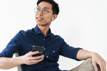 Photo of cheerful chinese businessman 20s wearing earpods sitting in chair and holding cell phone while working in office isolated over white background