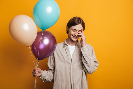 Laughing shy handsome man in shirt holding balloons with closed eyes over yellow background