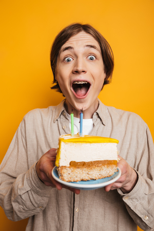 Vertical image of Surprised happy handsome man in shirt holding plate with cake and looking at the camera over yellow background Stock Photo