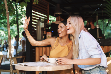 Two cheerful young girlfriends sitting at the cafe table indoors, waving hand Stock Photo