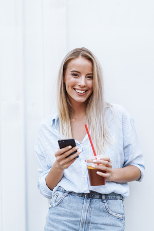 Smiling young blonde woman standing outdoors, using mobile phone, holding a drink with straw
